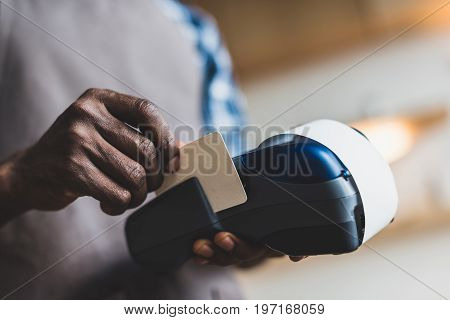cropped view of african american waiter making transaction with credit card in cafe