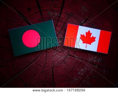 Bangladesh Flag With Canadian Flag On A Tree Stump Isolated