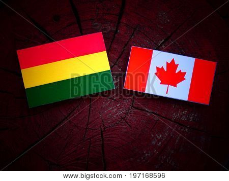 Bolivian Flag With Canadian Flag On A Tree Stump Isolated