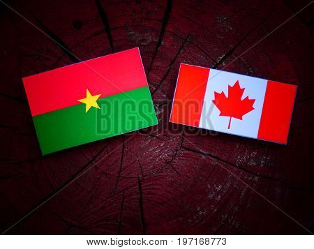 Burkina Faso Flag With Canadian Flag On A Tree Stump Isolated