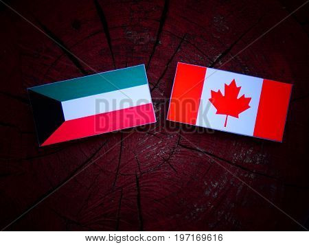 Kuwaiti Flag With Canadian Flag On A Tree Stump Isolated