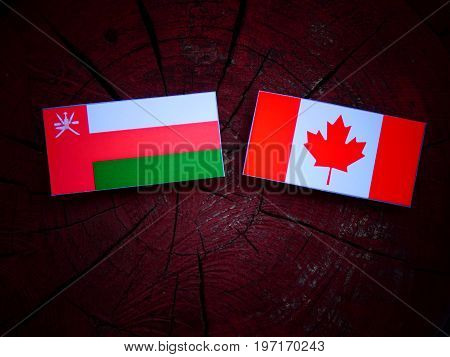 Omani Flag With Canadian Flag On A Tree Stump Isolated