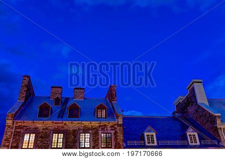 Skyscape of blue hour vibrant sky and European French building rooftops during evening