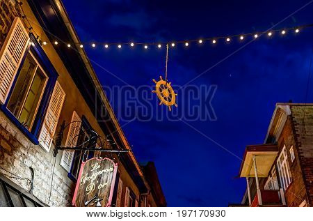 Quebec City Canada - May 31 2017: Lower old town street Rue du Petit Champlain with hanging decorations by restaurant