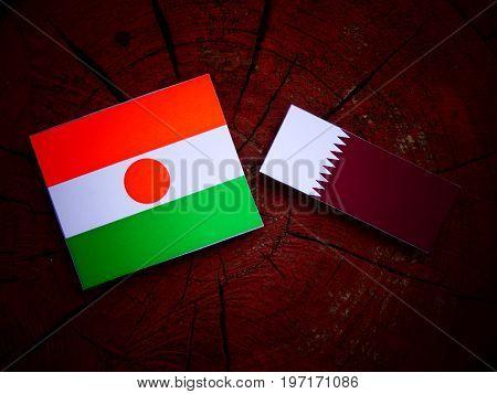 Niger Flag With Qatari Flag On A Tree Stump Isolated