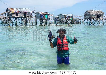 Semporna,Sabah,Malaysia-Apr 23,2017:Happy traveler man photographer with professional camera at floating village in Bodgaya island in Semporna,Sabah,Borneo,Malaysia.