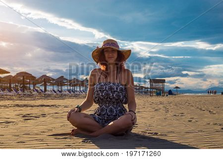 Happy Cheerful Summertime Woman Wearing Dress And Hat Sitting On The Beach With Arms Resting On Legs