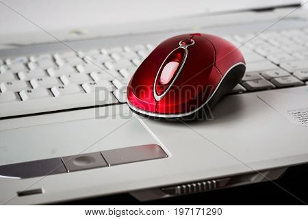 A beautiful red wireless mouse on the white keyboard of a laptop. Shallow depth of field
