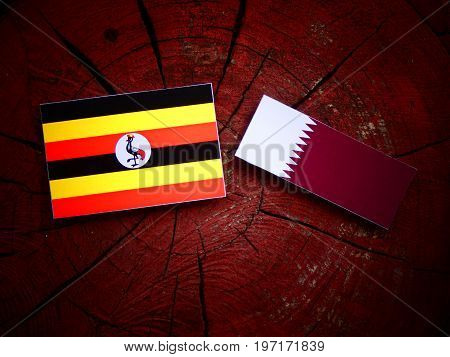 Uganda Flag With Qatari Flag On A Tree Stump Isolated