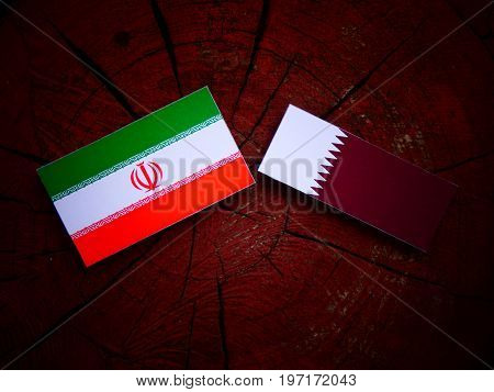 Iranian Flag With Qatari Flag On A Tree Stump Isolated