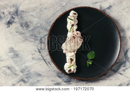 Food plating french dessert chocolate meringue with fresh mint, whipped cream and coffee beans served with cane sugar on black plate over gray concrete texture background. Flat lay, space