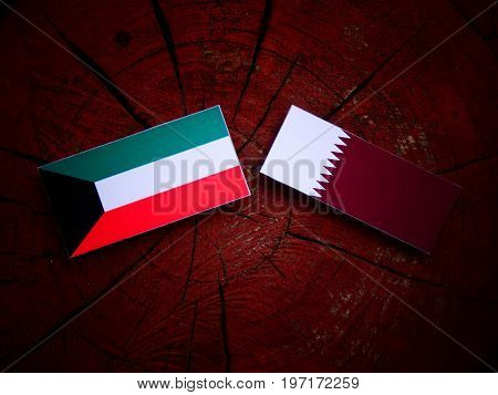 Kuwaiti Flag With Qatari Flag On A Tree Stump Isolated