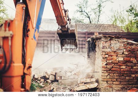 Industrial Close Up Of Excavator Using Scoop For Demolishing Old House And Ruins