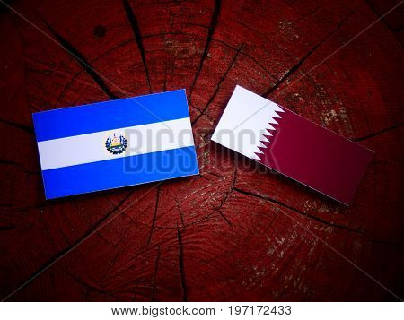 El Salvadoran Flag With Qatari Flag On A Tree Stump Isolated
