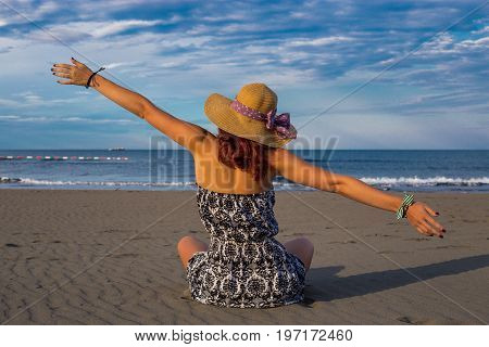 Beautiful girl woman in dress and hat sitting on the beach closeup with back turned and arms widespread with blue sea and sky in the background