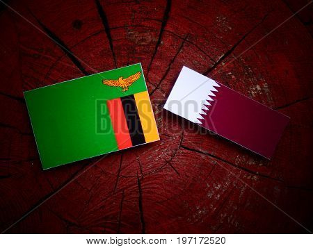 Zambian Flag With Qatari Flag On A Tree Stump Isolated