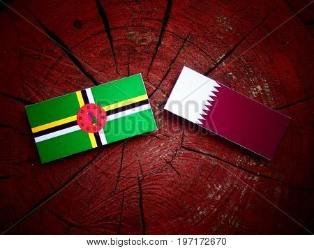 Dominica Flag With Qatari Flag On A Tree Stump Isolated