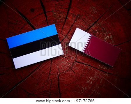 Estonian Flag With Qatari Flag On A Tree Stump Isolated