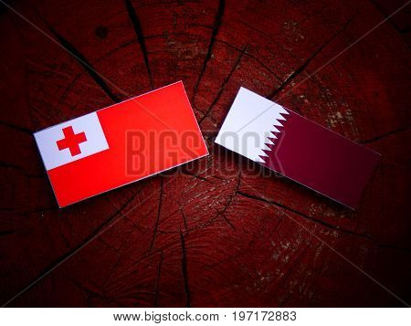 Tongan Flag With Qatari Flag On A Tree Stump Isolated
