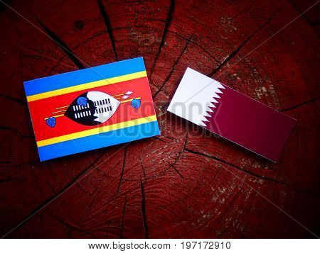 Swaziland Flag With Qatari Flag On A Tree Stump Isolated