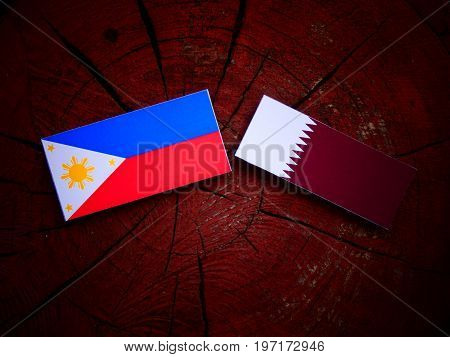 Philippines Flag With Qatari Flag On A Tree Stump Isolated