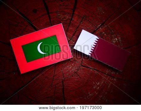 Maldives Flag With Qatari Flag On A Tree Stump Isolated