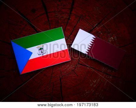 Equatorial Guinea Flag With Qatari Flag On A Tree Stump Isolated