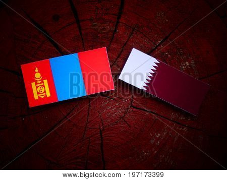 Mongolian Flag With Qatari Flag On A Tree Stump Isolated