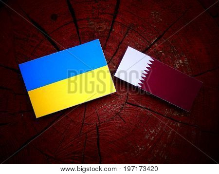 Ukraine Flag With Qatari Flag On A Tree Stump Isolated