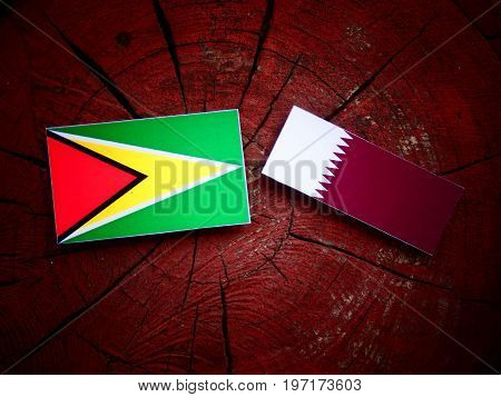 Guyana Flag With Qatari Flag On A Tree Stump Isolated