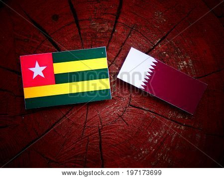 Togolese Flag With Qatari Flag On A Tree Stump Isolated