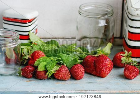 Fresh ripe garden strawberries and melissa herbs with empty glass and vintage metal jars for jam on blue white wooden kitchen table. Rustic style, day light, copy space