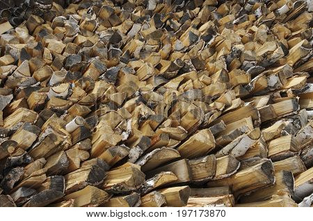 Firewood from birch folded into a woodpile to heat the house in winter