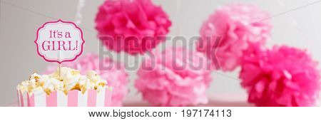 It's a girl sign in a popcorn bag at the baby shower party.  Paper flowers background. Baby shower celebration concept. Festive party background. Horizontal, wide screen format, banner format