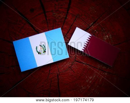 Guatemalan Flag With Qatari Flag On A Tree Stump Isolated