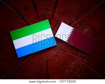 Seirra Leone Flag With Qatari Flag On A Tree Stump Isolated