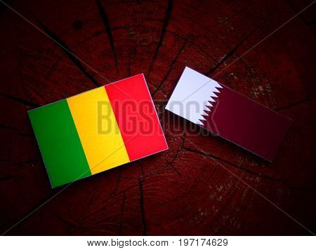 Malian Flag With Qatari Flag On A Tree Stump Isolated
