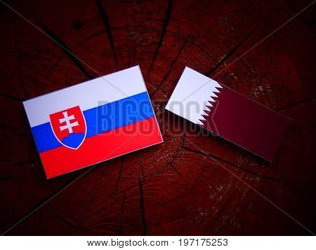 Slovakian Flag With Qatari Flag On A Tree Stump Isolated