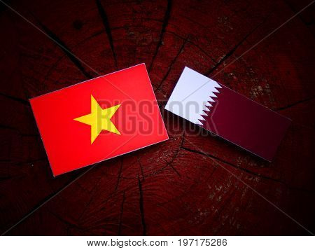 Vietnamese Flag With Qatari Flag On A Tree Stump Isolated