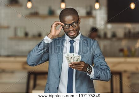 Handsome Sly African American Businessman In Eyeglasses Holding Money