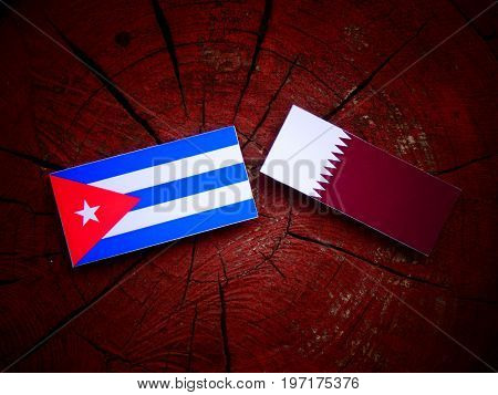 Cuban Flag With Qatari Flag On A Tree Stump Isolated