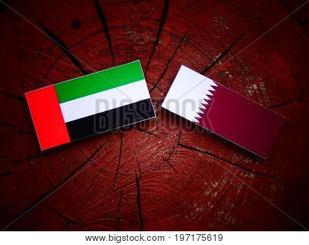 United Arab Emirates Flag With Qatari Flag On A Tree Stump Isolated
