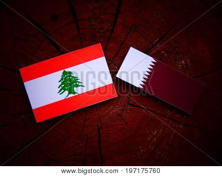 Lebanese Flag With Qatari Flag On A Tree Stump Isolated