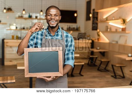 Smiling Male African American Owner Of Coffee Shop Holding Little Empty Blackboard In Wooden Frame