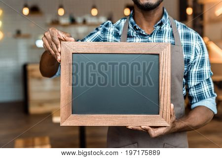 Cropped View Of Male African American Owner Of Coffee Shop Holding Little Empty Blackboard In Wooden