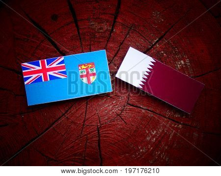Fijian Flag With Qatari Flag On A Tree Stump Isolated