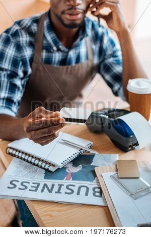 Cropped View Of African American Man Working With Credit Card Reader And Smartphone In Coffee Shop