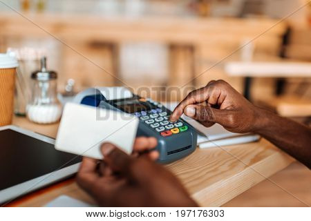 Cropped View Of African American Owner Working With Credit Card And Terminal In Coffee Shop