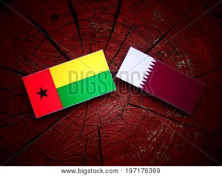 Guinea Bissau Flag With Qatari Flag On A Tree Stump Isolated