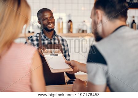 Handsome Cheerful African American Barista Giving Menu To Clients On Bar Counter In Cafe